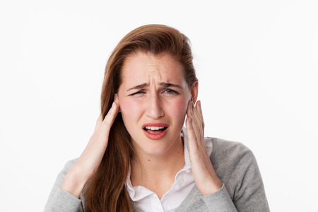tinnitus concept - frustrated young woman having painful headache,covering closed ears,annoyed by loud noise not wanting to hear their side of story