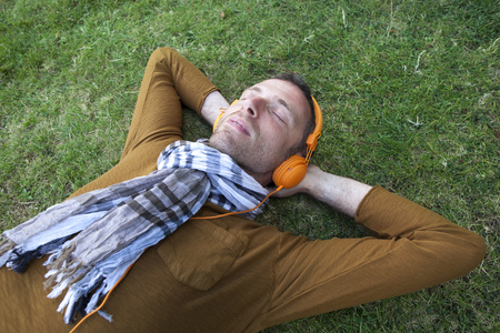 eyes closing: outdoors music - relaxed middle age man listening to cool music outside lying on grass,wearing trendy casual clothes resting with hands behind head,closing eyes to escape Stock Photo