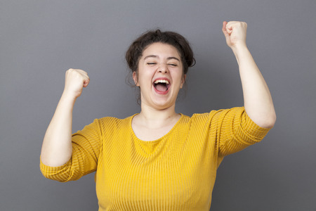success concept - laughing young fat girl wearing a yellow sweater expressing her achievement and joy with hands up Фото со стока - 46995019