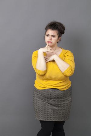 jonge dikke meisje met bruin haar en gele trui denken met een vinger op de lippen voor meditatie en plezier reflectie