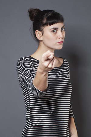 blaming: blaming young brunette woman staring at someone with index finger forward accusing and condemning someone with severity