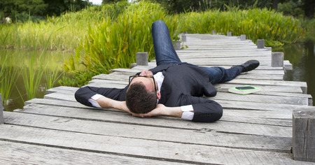lunchtime: Caucasian modern businessman with hands behind head lying on wood bridge daydreaming and relaxing in city park to think and enjoy lunchtime, back view in daylight