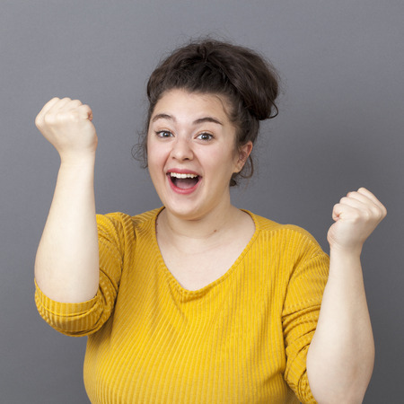 overweight girl: success concept - happy young overweight girl wearing a yellow sweater expressing her achievement and joy with both hands up Stock Photo