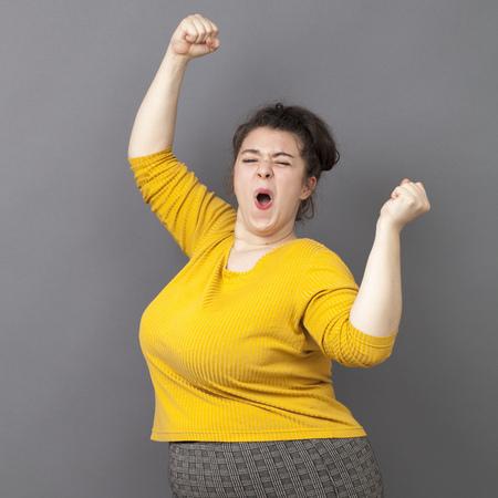 succes concept - opgewonden jonge overgewicht meisje draagt een gele trui uiten van haar prestatie en vreugde met handgebaar