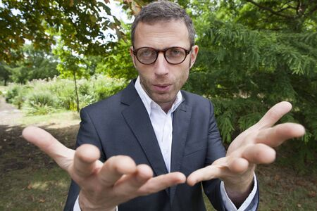 mad scientist: mad scientist outdoor concept - strange focused businessman showing his hands in foreground in green environment for corporate involvement,natural summer daylight Stock Photo