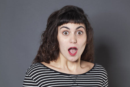 dropping: surprise and disappointment concept - portrait of a 20s brunette woman with jaw dropping and confused eyes wide open,studio shot Stock Photo