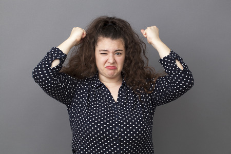 exasperation: angry overweight 20s woman expressing exasperation and frustration with both fists up and funny face Stock Photo