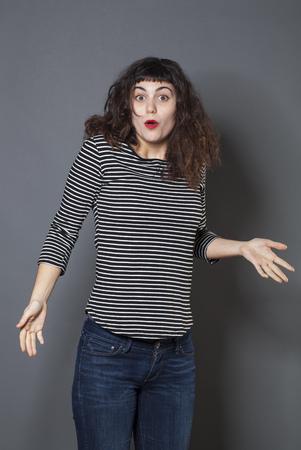 decepci�n: sorpresa y decepci�n concepto - 20s mujer morena asombrados y confusos con gesto de la mano y los ojos de par en par, tiro del estudio