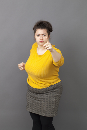 blaming: bullying oversize young woman staring at someone with finger pointing forward with blaming attitude and self-assurance