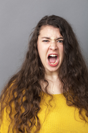 impatience: stressed out overweight 20s woman with long brown hair shouting loud for expressing rage and impatience Stock Photo