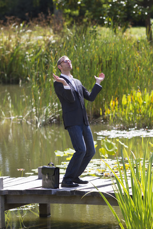 euphoria: celebrating success outdoors concept - thrilled modern businessman applauding himself with euphoria for  corporate achievement on bridge near water,natural summer daylight