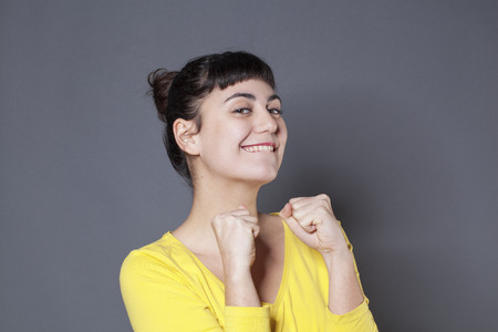winning woman: success concept - thrilled young woman with a yellow sweater expressing her victory and happiness