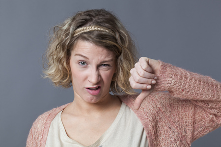 unhappiness: disappointment concept - unhappy young woman with curly blond hair making a thumb down with funny face for discouragement and unhappiness Stock Photo