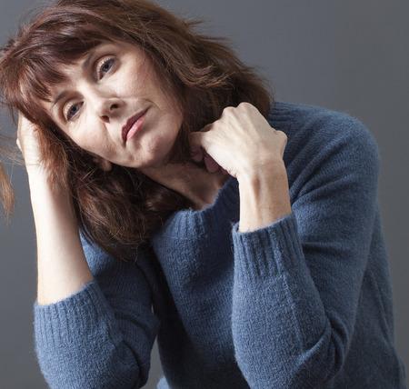 mujer reflexionando: mujer cansada de los años 50 con la cabeza y el pelo para la depresión, la pérdida o la fatiga debido a la menopausia Foto de archivo