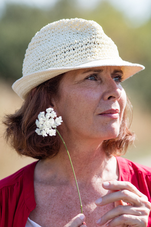 field of flower: wellbeing in countryside - closeup of beautiful senior woman with summer hat thinking,alone with field flower in hand,natural summer daylight