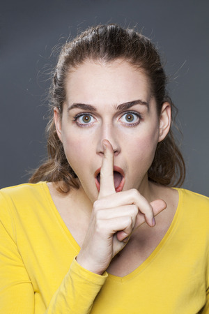 discretion: fun silence concept - stunned 20s girl wearing yellow sweater asking for discretion with a finger on lips,studio shot Stock Photo