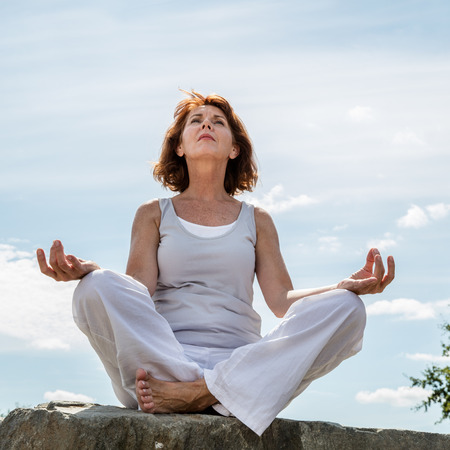 inner beauty: senior zen - beautifully aging woman sitting on a stone in yoga lotus position, wearing white, seeking serenity and balance in a park,summer daylight,low angle view Stock Photo