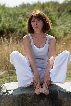 paz interior: zen alto - 50s tristes yoga mujer madura sentado en una piedra, que llevaba un traje de yoga que buscan para la reflexión y la paz interior al aire libre en la luz del día verano Foto de archivo