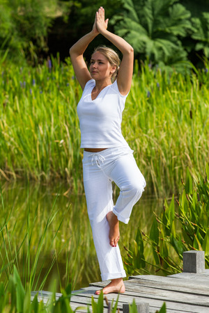 paz interior: al aire libre de la meditación - yoga mujer joven y sonriente el ejercicio de equilibrio, centrado en la paz interior para relajarse y meditar con el fondo verde y el agua, la luz del día verano Foto de archivo