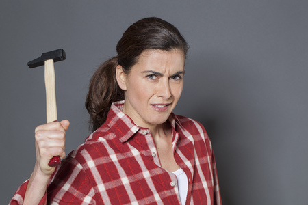 fed up: female DIY concept - dubious brunette woman holding hammer with strength,losing temper or fed up at having to work manually