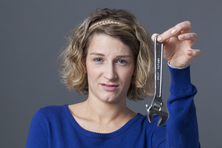 manual work: female DIY concept - disgusted young blond woman holding wrench as symbol of manual work and mechanics handiwork Stock Photo