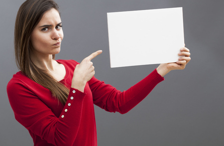 point of demand: judge mental young lady pointing at a blank message on board and wearing a red sweater