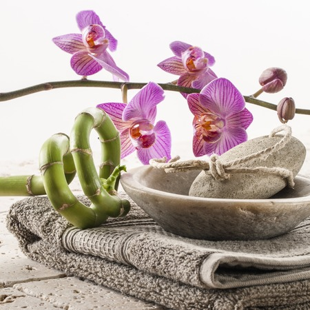 inner beauty: pedicure and foot care set with pumice stone on cotton towel and flowers zen