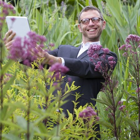 mad scientist: tablet usage outdoors - excited mad scientist or botanist making a selfie or photo with tablet standing alone in middle of jungle of long exotic green grass and flowers,natural summer daylight Stock Photo