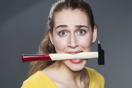 manual work: female DIY concept - embarrassed beautiful young woman biting hammer for questioning manual work or building handwork