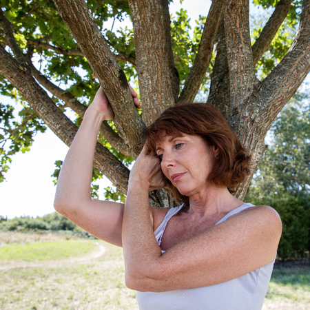 summer tree: senior green wellness - thinking mature woman holding tree branches in harmony with nature finding energy and balance in green environment,summer daylight