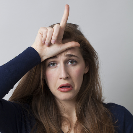 l hand: sad young woman making the L sign on forehead for loser message, cool hand gesture for youth culture Stock Photo