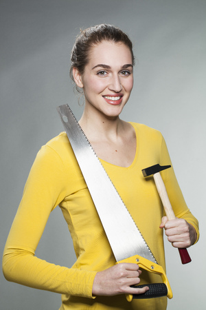 prove: female DIY concept - smiling beautiful young woman holding saw and hammer to prove her home handiwork expertise