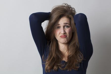 desilusion: concepto decepción - mujer joven avergonzada con el pelo largo y castaño echar a perder su pelo para expresar su pesar o renuncia
