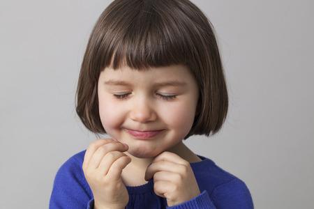 eyes closing: smiling 4 year-old girl enjoying closing her eyes for hide-and-seek
