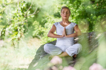 inner peace: outdoors meditation - young yoga woman exercising in lotus praying pose,closing eyes to focus on inner peace to relax and meditate on a big stone,green blurred foreground and background