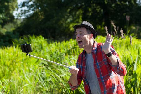 selfy: male selfy concept - laughing middle age man with a casual hat enjoying taking a selfie with a stick in water grass in city park,summer natural daylight