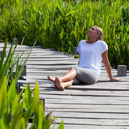bare feet: relaxation outside - beautiful young woman with bare feet daydreaming, lying on a wooden bridge in green environment, summer daylight Stock Photo