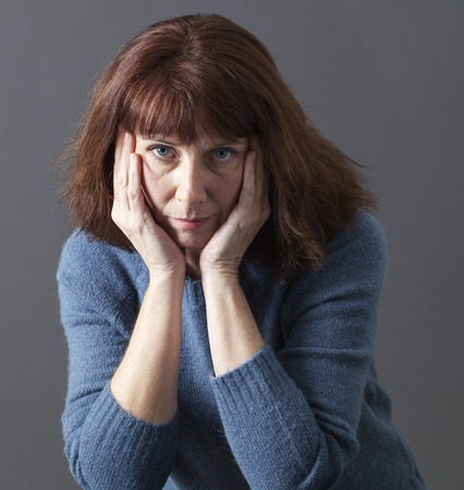 affective: portrait of mature woman with brown hair and blue winter sweater thinking,face leaning on both hands,staring with sadness