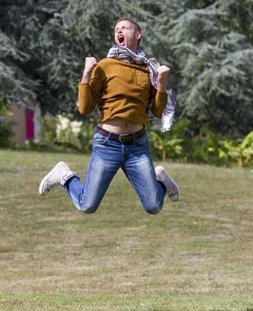 extrovert: celebrating success outdoors concept - dynamic modern man jumping with arms raised with strength for achievement and happiness in green park,natural summer daylight