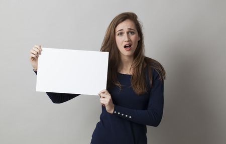 sad girl: surprised young woman holding a banner with a blank text Banque d'images