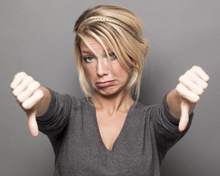 失望コンセプト - 意見の相違や落胆のダウン ダブル親指を作る悲しい若い金髪女性