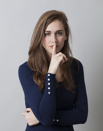 austere: secret and taboo concept - serious 20s girl wearing navy blue sweater asking for silence with finger on lips,studio shot