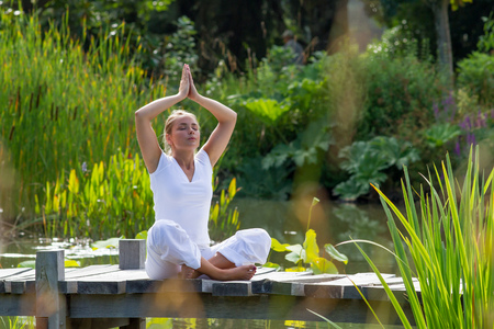 relaxed: outdoors meditation - relaxed young yoga woman in praying lotus pose,closing eyes to relax and meditate on a wooden bridge with green foreground and water background, summer daylight Stock Photo