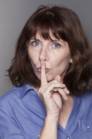 taboo: secret and taboo concept - teacher-like 50s woman wearing blue shirt asking for silence with finger on lips,studio shot Stock Photo