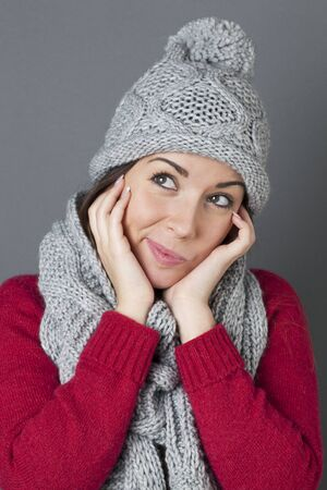 winter hat: trendy warm winter - cute young woman daydreaming and smiling with her comfortable and warm winter hat and scarf