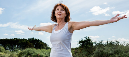chakra energy: senior zen - radiant mature woman opening her chakra and arms wide,seeking for energy and harmony with nature, green foreground and blue sky in summer daylight