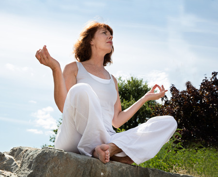 senior yoga: senior zen - senior yoga woman sitting on a stone seeking for harmony and concentration outdoors,summer daylight,low angle view