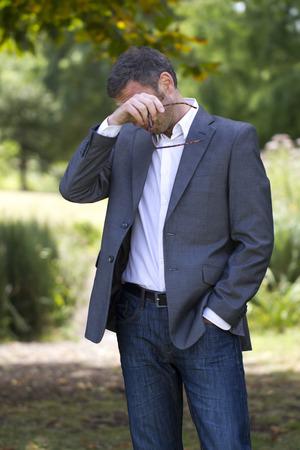 ojos llorando: alergias - enfermo empresario de mediana edad con picazón en los ojos quitándose las gafas de fatiga o fiebre del heno alergias en el parque, la luz del día verano naturales Foto de archivo