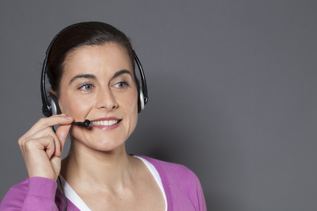 answering phone: focused 30s female operator answering the phone with earphones