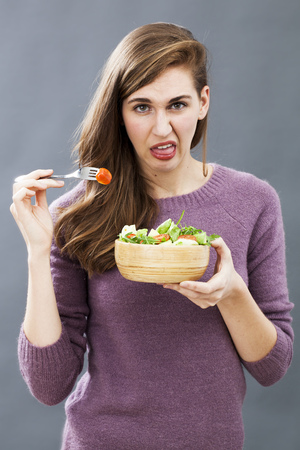 woman eating fruit: disgusted young girl being picky at eating mixed green salad with cherry tomatoes as vegetarian diet Stock Photo